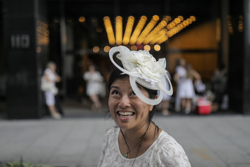A woman poses as she travels to the ferry to Diner En Blanc, a secret pop up dinner, held this year on Governors Island in New York