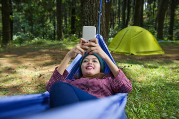 Smiling asian woman with phone resting in hammock