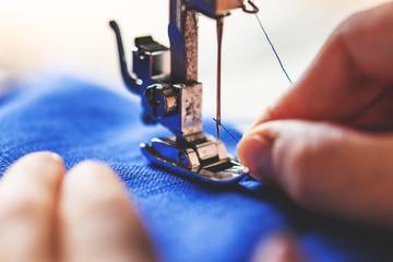 Einfädeln von Faden in die Nähnadel einer Nähmaschine, blauer Stoff