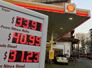 An employee pumps fuel as petrol prices are seen on a billboard at a Shell petrol station in Buenos Aires