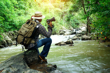 Nature photographer will take photos calm water stream around the rocks in forest