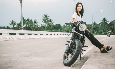 a women wearing a white shirt was sit on a back motorcycle and she smiling happily