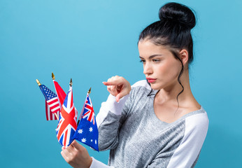 Young woman with learn English theme with the flags of English speaking countries on a blue background