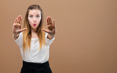 Young woman making a rejection pose on a brown background