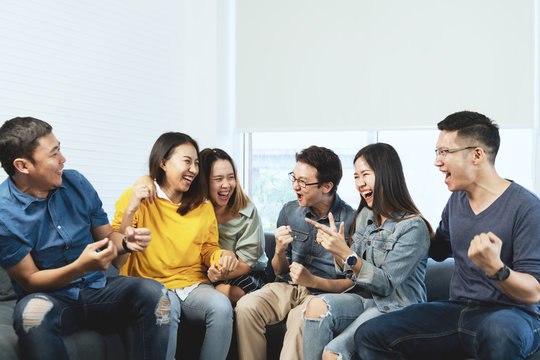 Young Attractive asian group of friends talking and laughing with happy in gathering meeting sitting at home feeling cheerful and enjoy game in leisure time together. People in blue or yellow wearing.