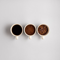 Coffee cups / Creative concept photo of three coffee cups on grey background.