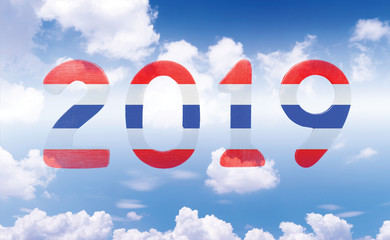 New year 2019 concept. Wooden numbers 2019 against on bright sky and clouds background. The numbers flag of Thailand.