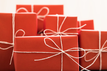 holiday congratulation and valentine day present. gifts in red packaging tied with white twine. selection of boxes on white background.