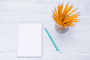 a glass of simple pencils on a blue desktop, there is a place on a blank sheet for recording
