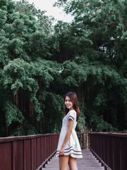The girl wearing white dress and she is standing on the red wood bridge with tree and canal background , style dark green tone, bang krachao island in samut prakan at Thailand