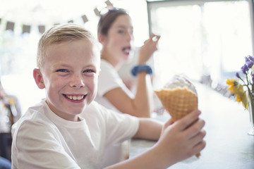 Smiling Children enjoying ice cream cones at an ice cream parlor. Little boy with a waffle cone is enjoying some delicious ice cream