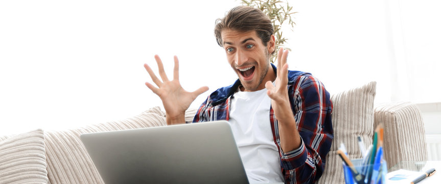 surprised young man with laptop sitting on sofa