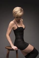 Fashion blond girl in black short dress on chair