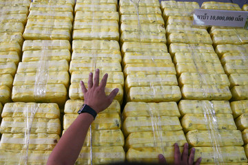A police officer arranges seized drugs before a news conference at Office of the Narcotics Control Board in Bangkok