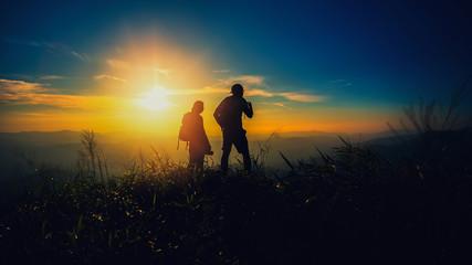 silhouette couple hiker watching through binoculars on the top of mountain