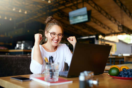 Portrait of happy young business woman celebrating success with arms up in front of laptop. Mixed race female won a lot of money in lottery prize, raised arms with fists. Freelancer finished project.