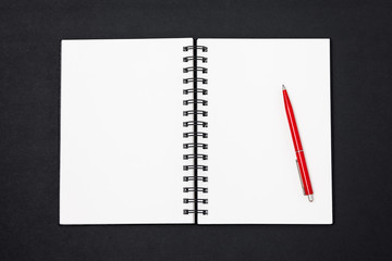 Top view of open spiral blank notebook with red pen on black desk background