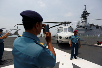 Indonesian Navy officers take pictures on the deck of the Japan Maritime Self-Defense Force helicopter carrier JS Kaga (DDH 184) after it arrived at Tanjung Priok Port as part of an Indo-Pacific tour in Jakarta