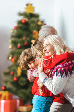 grandparents embracing with kids on christmas at home