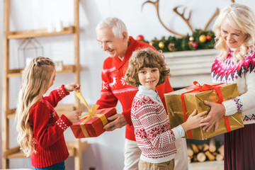 grandparents and happy kids with gift boxes spending time together on christmas