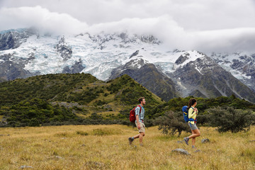 Wall Mural - New Zealand travel hikers hiking on snow capped mountains landscape background. Couple trampers walking on Hooker Valley Track, popular tourist destination for summer vacation.
