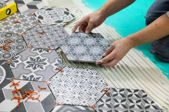 flooring - man laying hexagon tiles on the floor