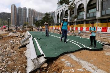 People walk through a damaged path after Super Typhoon Mangkhut hit Hong Kong