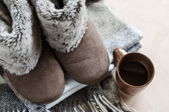 Warm home clothes. Woolen plaid and home slippers and cup of hot drink.