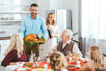happy family with turkey celebrating thanksgiving day at home