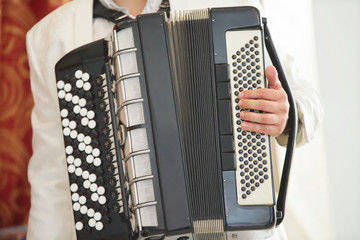 Musical instrument accordion in the hands of a male.