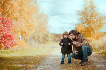 Father and daughter walking together, autumn day