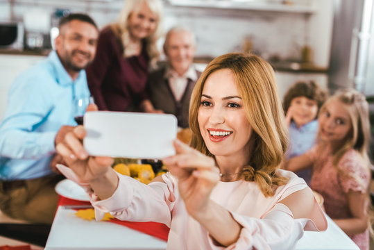 happy young woman taking selfie with her family during thanksgiving dinner