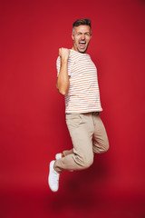 Full length photo of successful man in striped t-shirt screaming and clenching fists, isolated over red background