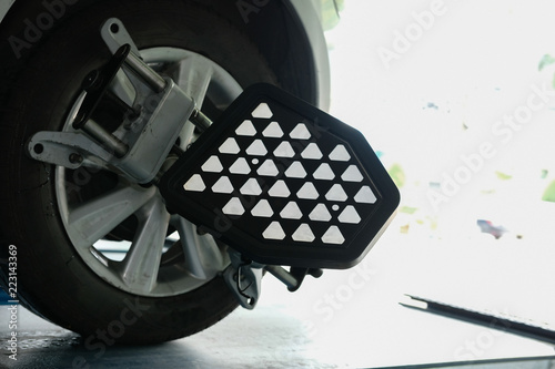 car tyre clamped with aligner reflector adjustment tool for