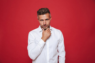 Handsome guy with stubble in white shirt looking on camera, isolated over red background