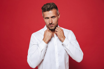 Fancy brunette man 30s with stubble in white shirt looking on camera, isolated over red background