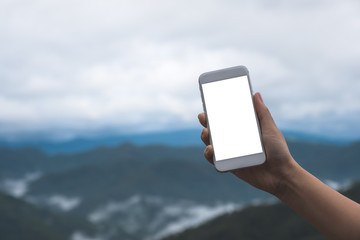 Mockup image of a hand holding and showing white smart phone with blank desktop screen in outdoor with blur green mountains background