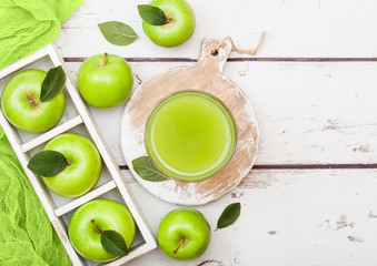 Glass of fresh organic apple juice with granny smith green apples in box on wooden background