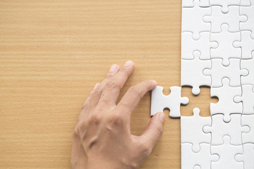 hand placing the last jigsaw puzzle piece,conceptual of problem solving