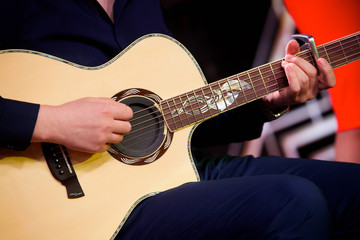 Stringed musical instrument acoustic guitar in the hands of a male musician.