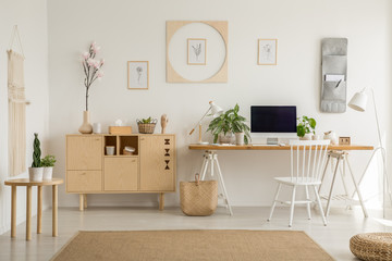 Wooden cupboard next to desk with desktop computer and plants in home office interior. Real photo