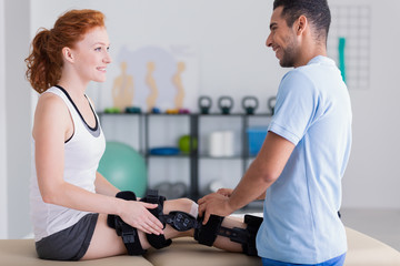Smiling professional physiotherapist helping woman with leg injury