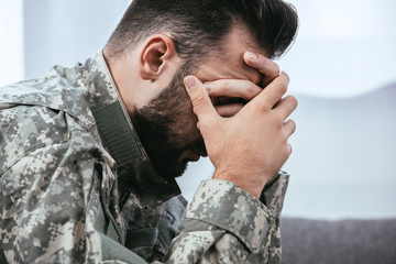 side view of depressed army man in military uniform with post-traumatic stress disorder holding his head