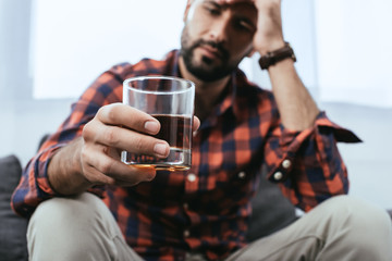 Photo sur Aluminium Alcool close-up shot of depressed young man with glass of whiskey