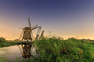 Beautiful traditional historic windmill near Baambrugge and Abcoude in the Netherlands at night with a nice reflection and lots of stars in the sky