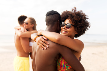 friendship, summer holidays and people concept - happy friends or couples hugging on beach