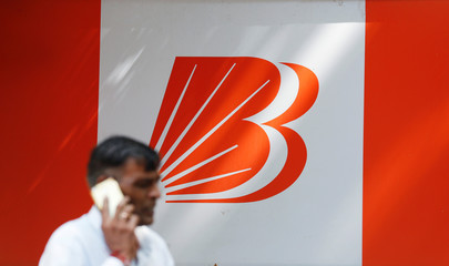 A man talks on mobile phone in front of the Bank of Baroda logo in New Delhi