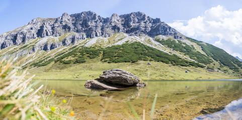 Klarer Bergsee in den Alpen, dahinter Gipfel und blauer Himmel