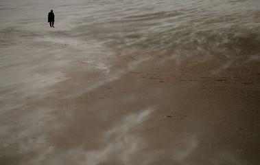 A woman walks along the beach through blowing sand in New Brighton