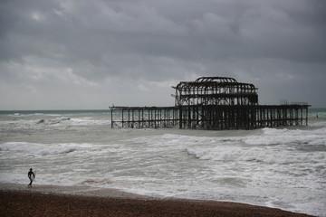 A surfer walks along the beach in Brighton